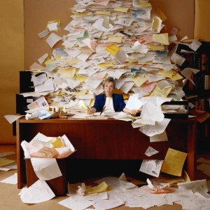 woman overwhelmed with paper at work